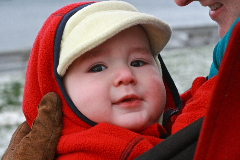 baby smiling in snowsuit