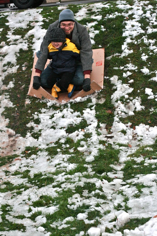 dad and boy sledding on cardboard box in winter outdoors in Seattle