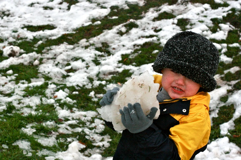 boy picking up snowball in winter outdoors in Seattle