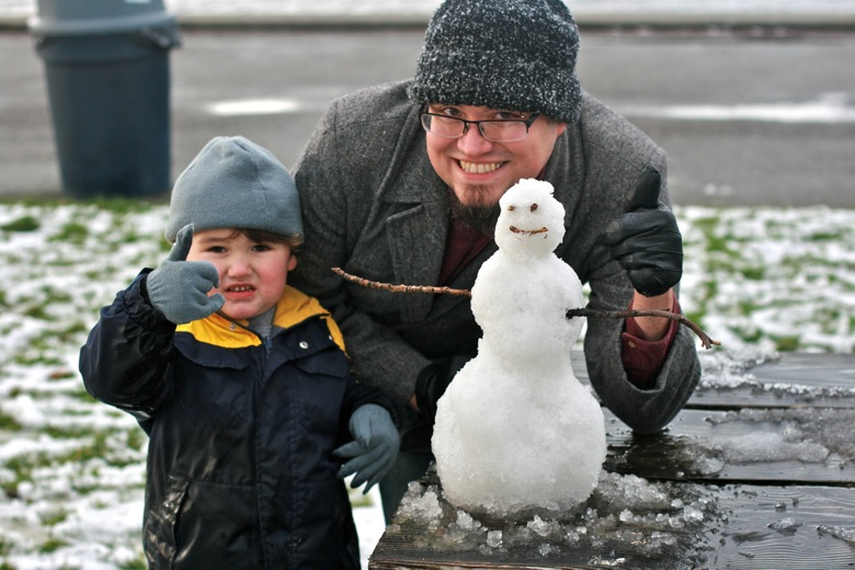 building mini snowman outdoors Seattle — dad and son