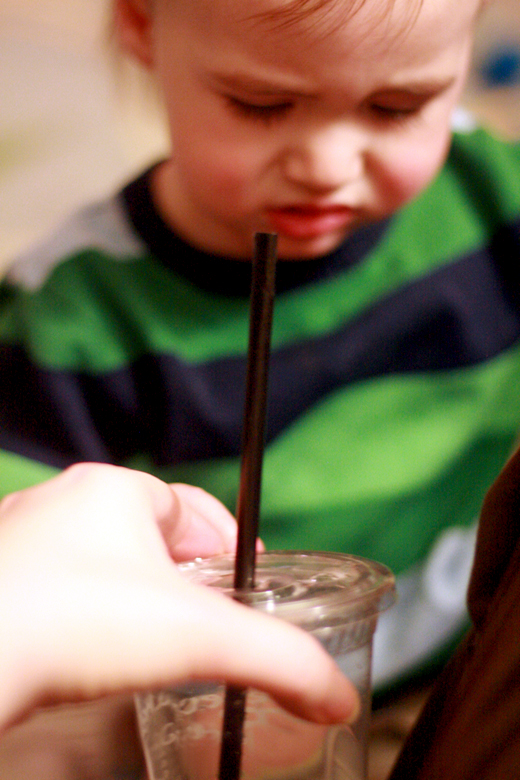 baby offered water with straw in a cup