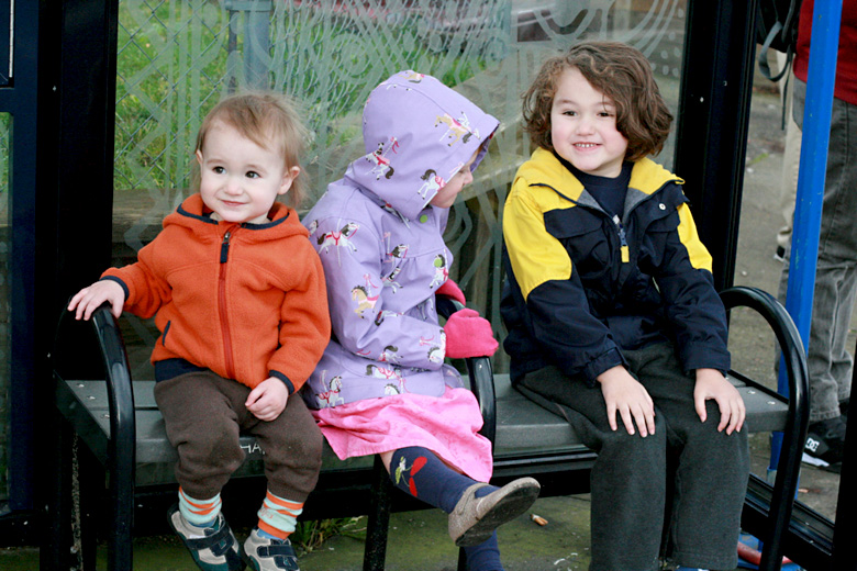 three kids on a bus stop bench - portland trip travel