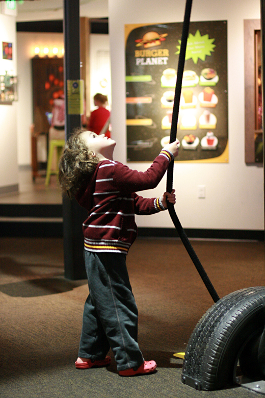 boy tugging rope pulley - pacific science center outing seattle unschooling