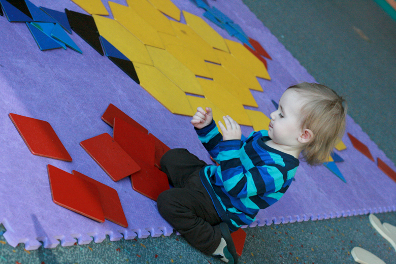 toddler putting together giant floor puzzle - pacific science center outing seattle unschooling