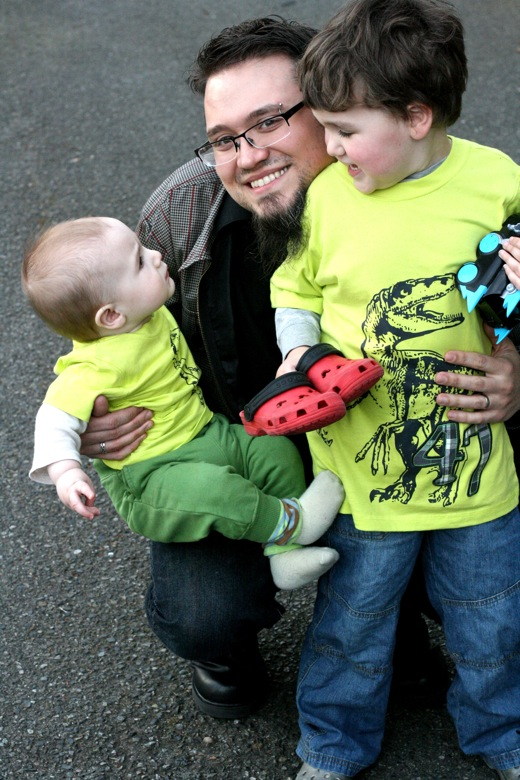 two matching boys — dad, baby and brother in dinosaur t-shirts