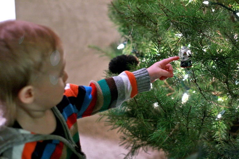 baby points to ornament on the tree — christmas12 holidays alrik a1yo a18mo