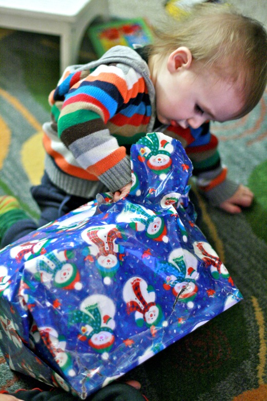baby peeks inside present while unwrapping — christmas12 holidays alrik a1yo a18mo