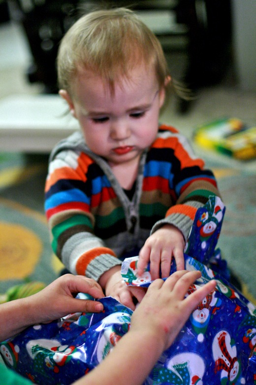 baby toddler unwraps present —christmas12 holidays alrik a1yo a18mo