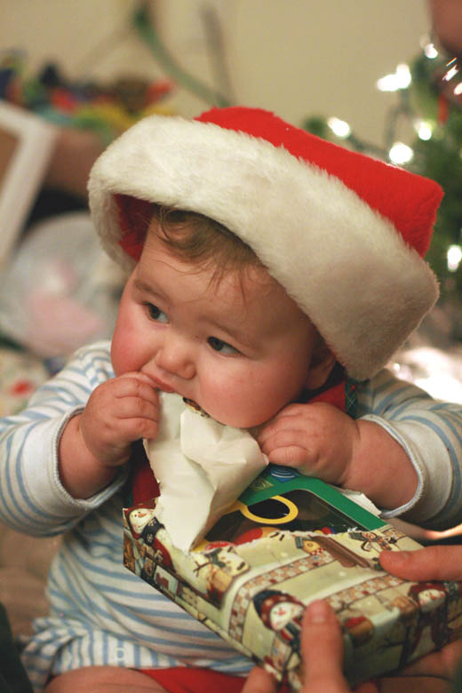 baby in Santa hat eating wrapping paper