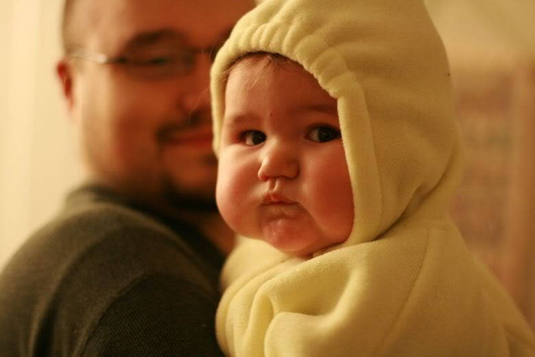 baby in a snowsuit held by father