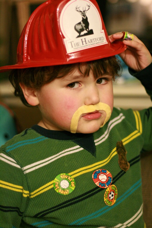 serious boy wearing mustache and firefighter hat