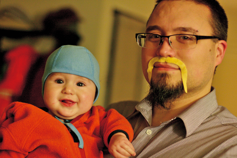 dad with fake mustache with smiling baby in aviator hat