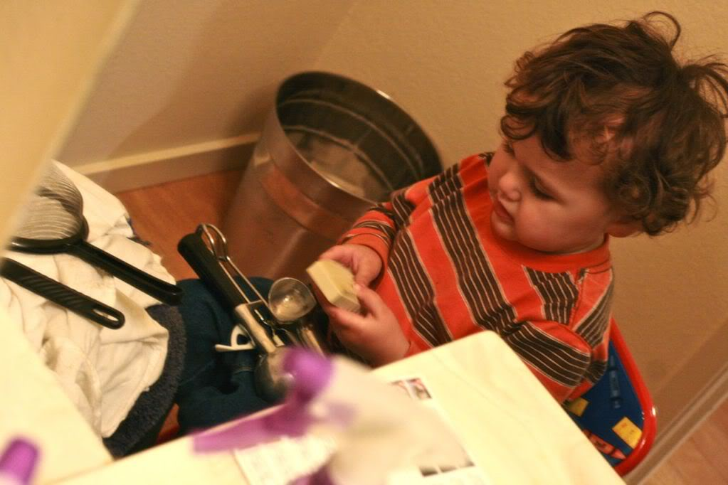 toddler playing in bathroom with kitchen implements