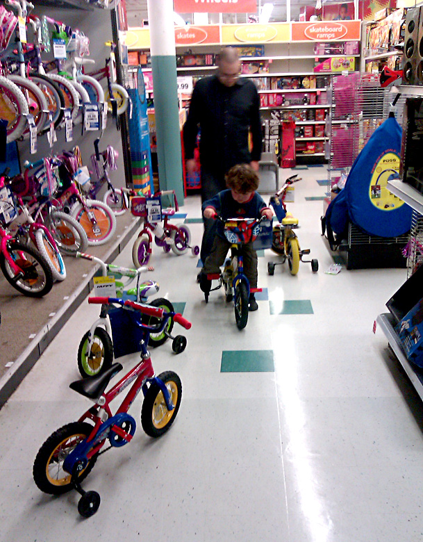 trying out children's bicycles at the toy store