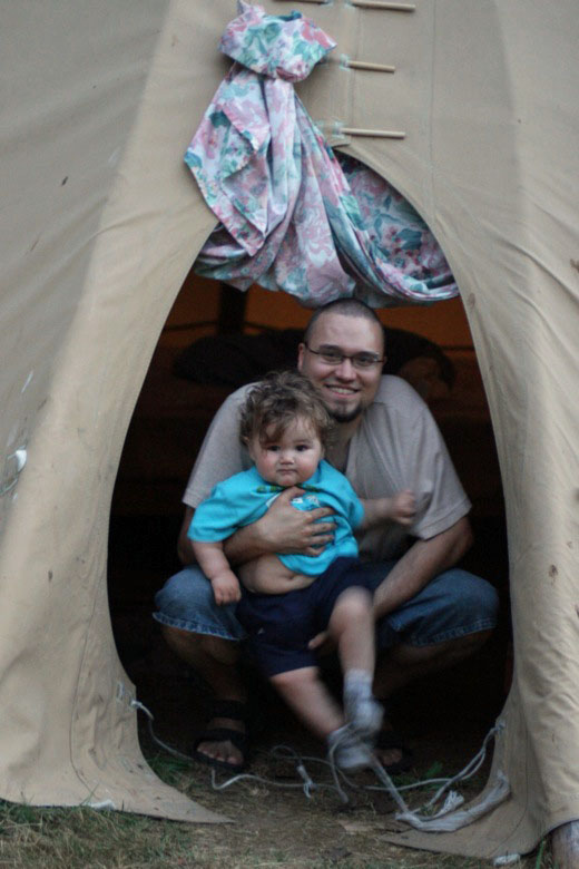 dad and boy in teepee while camping